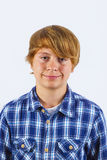Portrait of a teen boy with blonde hair wearing a checked shirt Stock Image