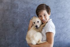 Teen boy with golden retriever. Portrait of teen boy with golden retriever by the wall stock image