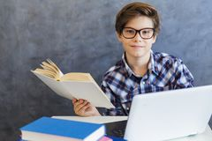 Teen boy reading book and use laptop at home. Portrait of teen boy reading book and use laptop at home Royalty Free Stock Photos