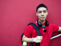 Portrait of a teen with a cap on and ear phones. Portrait of a male teenager wearing a reversed cap and a pair of ear phone resting on his neck Royalty Free Stock Photography
