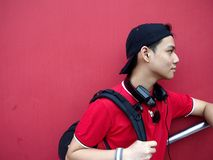 Portrait of a teen with a cap on and ear phones. Portrait of a male teenager wearing a reversed cap and a pair of ear phone resting on his neck Royalty Free Stock Photo