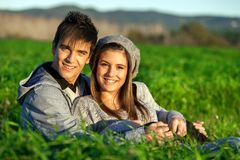 Portrait of teen couple sitting in grass field. Royalty Free Stock Photography