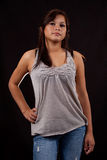 Portrait of teen girl. Attractive young aboriginal teen girl  wearing jeans and grey top standing over black Stock Images