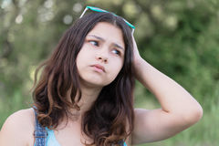 Portrait of teen girl busy problems in summer nature Stock Photo