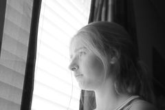 Portrait of a teen girl looking out a window Stock Photo