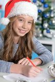 Teen girl writing letter. Portrait of teen girl in Santa hat writing letter Royalty Free Stock Photo