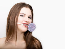 Portrait of teen girl showing dental braces and holding candy stock photography