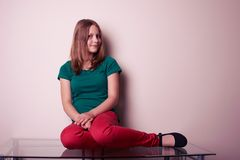 Portrait of a teen girl sitting on table Royalty Free Stock Photo