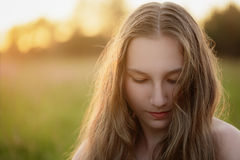 Portrait of teen girl in sunset looking down Royalty Free Stock Image