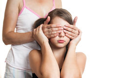 Portrait of a teen girl surprising her mother by covering eyes Royalty Free Stock Photo
