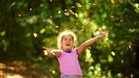 Portrait teen girl throws yellow leaves of autumn stock video