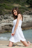 Portrait of a teen girl with white dress at the beach. Playful moment at summer holidays. Looking at the camera, full length body shoot in vertical Stock Photos