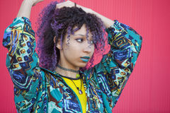 Portrait of a teen woman with purple afro hair and blue lips on. Portrait of a teen woman with purple afro hair and blue lips isolated on pink background stock image