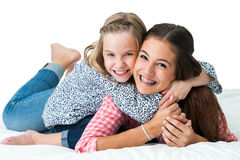 Portrait of teen and younger sister on bed. Stock Photography