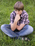 Portrait of teenage boy. On the grass background Royalty Free Stock Image