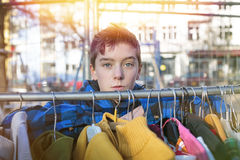 Portrait of a teenage boy behind a clothes rail Stock Photos