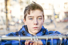 Portrait of a teenage boy behind a clothes rail Royalty Free Stock Photography