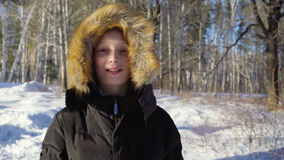 Portrait of a teenage boy close up. The boy smiles showing emotions. Sunny winter evening in the forest. Strong wind. Slow motion stock video