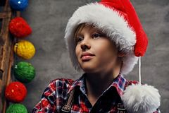 Portrait of teenage boy dressed in Santa`s hat and a plaid shirt. stock images