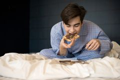 Boy Eating Crunchy Toast in Bed royalty free stock photos