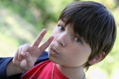 Portrait of a teenage boy gesturing. The teenager showing gesture victory Royalty Free Stock Photography