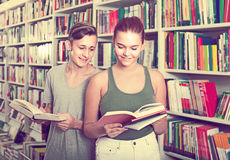 Portrait of teenage boy and girl customers looking at open book stock photography