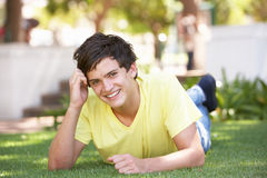 Portrait Of Teenage Boy Laying In Park Stock Images