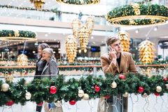 A portrait of teenage boy with smartphone in shopping center at Christmas. A portrait of teenage boy with smartphone in shopping center at Christmas, making a stock photography