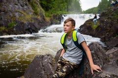 Portrait of a teenage boy standing near a waterfall Stock Image