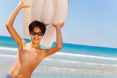 Sporty boy with swimming air mattress overhead. Portrait of teenage boy in sunglasses with swimming air mattress overhead against tropical seascape stock images