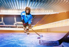 Boy learning to pass the puck at ice hockey rink stock photo