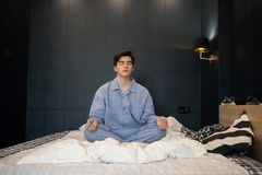 Boy Meditating on Bed. Portrait of teenage boy wearing pajamas meditating with eyes closed while sitting on bed in lotus position trying to sleep at night stock photo