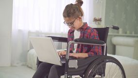 Portrait of a teenage disabled girl in a wheelchair using a laptop royalty free stock images