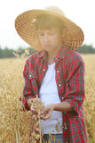 Portrait of teenage farmer boy holding oat seeds with outer shells in cupped palms with sun flare Royalty Free Stock Photography
