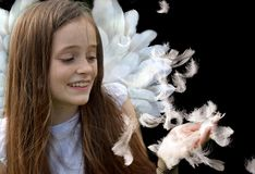 Teenage girl in angel costume catches flying feathers stock photos