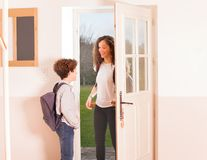 Happy children come back home from school. Portrait of teenage girl and boy with schoolbags, opening the front door come back home from school royalty free stock photo