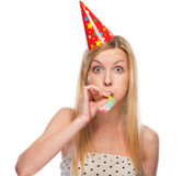 Portrait of teenage girl in cap blowing in party horn blower Stock Images