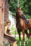 Portrait of teenage girl and chestnut horse near the wooden stab Royalty Free Stock Photos