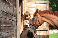 Portrait of teenage girl and chestnut horse near the wooden stab Stock Photo