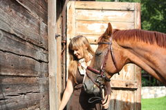 Portrait of teenage girl and chestnut horse near the wooden stab Royalty Free Stock Image