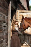 Portrait of teenage girl and chestnut horse near the wooden stab Stock Images