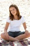Portrait teenage girl cross legged sitting. Portrait teenage girl on beach royalty free stock photos