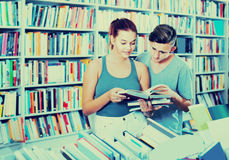 Portrait of  teenage girl customer looking at open book standing Royalty Free Stock Photo