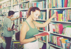 Portrait of  teenage girl customer looking at open book standing Royalty Free Stock Images