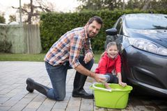 Teenage girl and father washing a car on a sunny day Royalty Free Stock Photo