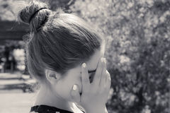 Portrait of a teenage girl with hand covering her face. Black an Stock Image