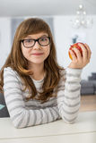 Portrait of teenage girl holding apple while sitting at table in house Stock Images