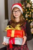 Portrait of teenage girl holding stack of Christmas presents Stock Photo