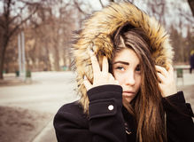 Portrait of a teenage girl outdoor. Portrait of a teenage girl with long beautiful hair outdoor wearing winter coat with the faux - fur hood on Stock Photography