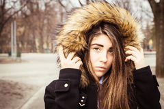 Portrait of a teenage girl outdoor. Portrait of a teenage girl with long beautiful hair outdoor wearing winter coat with the faux - fur hood on Stock Image